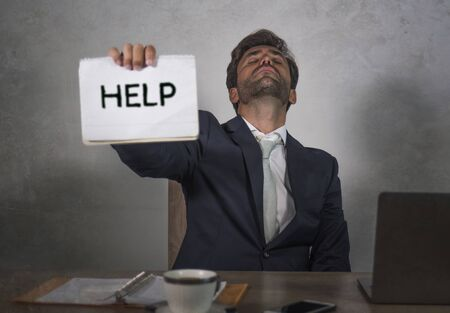 depressed and stressed attractive hispanic man in suit and tie working overwhelmed office computer desk holding notepad asking for help frustrated and overworked as businessman in trouble