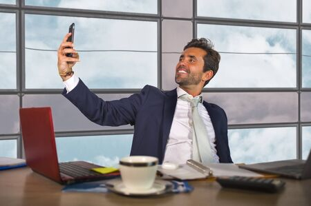 corporate business portrait of young happy and attractive latin businessman in suit and tie working at modern financial company taking selfie smiling confident celebrating successful project