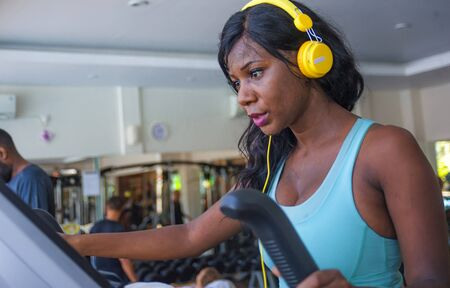 fitness lifestyle  portrait of young attractive and happy black afro American woman training at gym all doing elliptical machine workout listening to music with  headphones Stock Photo
