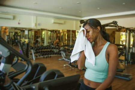 indoors gym portrait of young attractive black African American woman sweating training hard at fitness club after treadmill running workout wiping sweat with towel in sport and healthy lifestyle concept