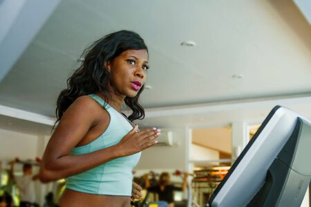 indoors fitness center lifestyle  portrait of young attractive and sweaty black afro American woman training hard at gym doing treadmill running workout in body care and healthy lifestyle concept