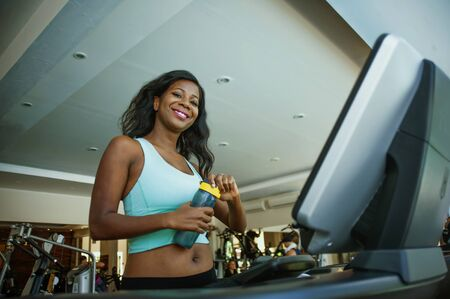 fitness center lifestyle portrait of young happy and attractive black African American woman at gym running on treadmill machine smiling cheerful walking warming up in sport and health care concept Stock Photo