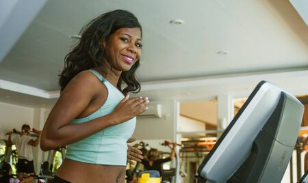 indoors fitness lifestyle  portrait of young attractive and happy black afro American woman training hard at gym all sweaty doing treadmill running workout in body care and healthy lifestyle