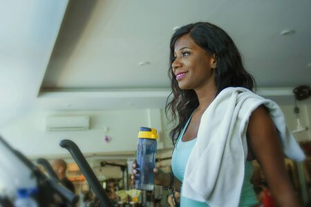 fitness center lifestyle portrait of young happy and attractive black afro American woman at gym running on treadmill machine smiling cheerful walking warming up in sport and health care concept 写真素材