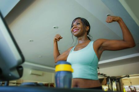 young attractive and happy black afro American woman training at gym doing treadmill workout fitness machine posing playful showing biceps muscle at sports club smiling cheerful Stock Photo