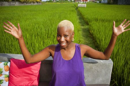 lifestyle natural portrait young attractive and happy black afro American hipster and cool woman posing playful outdoors at tropical rice field enjoying excited Summer holidays trip in Asia