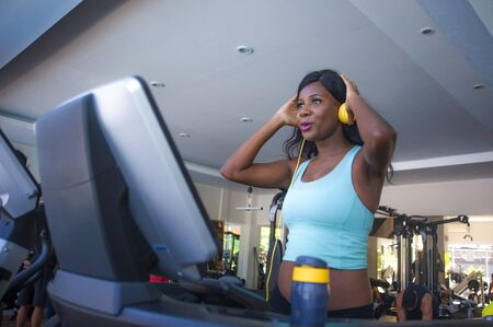 indoors fitness lifestyle  portrait of young attractive and happy black afro American woman training at gym all doing treadmill workout adjusting headphones listening to music
