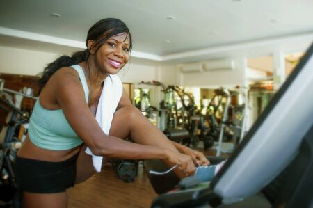 indoors portrait of young attractive and happy black afro American woman training at gym ties sport  shoes after hard treadmill running workout sweaty and satisfied in fitness healthy lifestyle