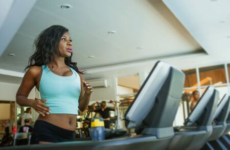 indoors fitness center lifestyle  portrait of young attractive and sweaty black African American woman training hard at gym doing treadmill running workout in body care and healthy lifestyle concept