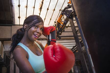 fitness center lifestyle portrait of young attractive and beautiful black afro American woman working out at gym training sweaty on heavy bag punching happy with boxing gloves
