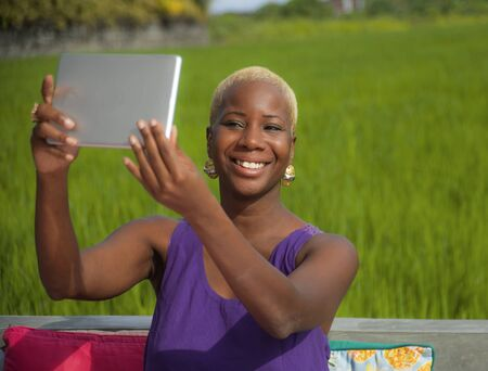 young attractive and happy black African american woman in cool hipster style taking selfie outdoors with digital tablet pad on rice field background enjoying Summer holidays travel in Asia
