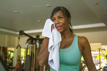 indoors gym portrait of young attractive black afro American woman sweating training hard at fitness club exhausted after treadmill running workout wiping sweat with towel in sport and health care