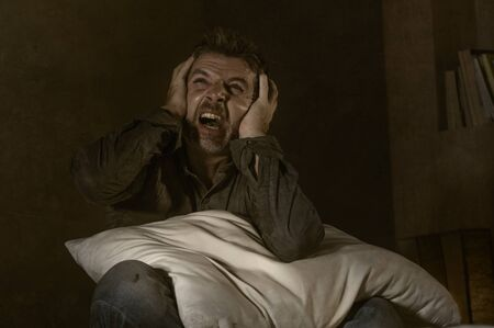 dramatic portrait of depressed and sick man suffering from psychosis illness or mental disorder looking weird and helpless in psychiatric and psychological problem concept Stock Photo