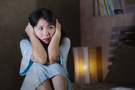 dramatic portrait of depressed and sick Asian Chinese woman suffering from psychosis illness or mental disorder looking weird and helpless in psychiatric and psychological problem concept