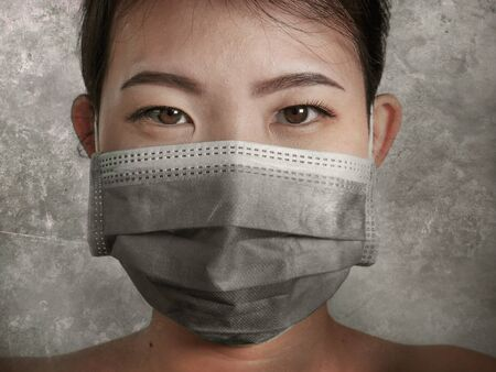 young beautiful Asian Chinese woman in protective face mask in prevention against Wuhan Coronavirus epidemic outbreak in China in virus transmission and infection concept  Stock Photo