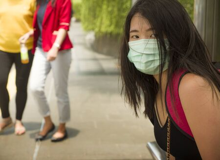 young beautiful and attractive Asian student woman walking on city street wearing protective facial mask against Corona virus epidemic outbreak spreading breathing syndrome