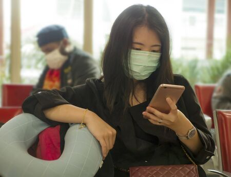 young beautiful tourist Asian Korean tourist girl at airport wearing protective facial mask checking internet news and information with mobile phone on Coronavirus epidemic outbreak