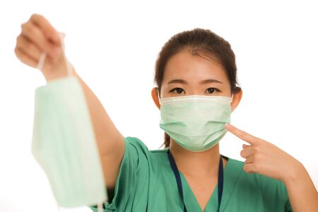 Coronavirus outbreak - young beautiful Asian Chinese medicine doctor woman or hospital nurse recommend use of protective face mask in prevention vs virus infection in health care Stock Photo