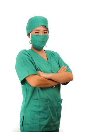 Asian Chinese woman as successful physician - young beautiful and attractive medicine doctor or chief hospital nurse in green scrubs and surgeon hat smiling confident behind surgical mask
