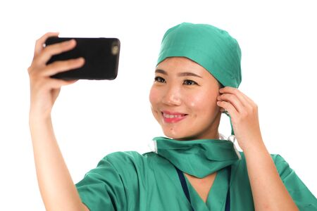 Asian Korean woman as successful taking selfie on hand phone - young beautiful and happy medicine doctor or hospital nurse taking self portrait on mobile phone smiling in surgical hat 写真素材