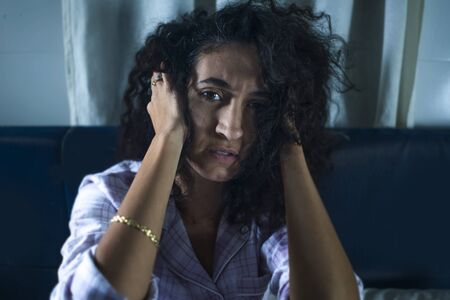 dramatic night lifestyle portrait of young sad and depressed hispanic woman with curly hair sleepless in bed awake and thoughtful feeling worried suffering depression problem and insomnia Фото со стока