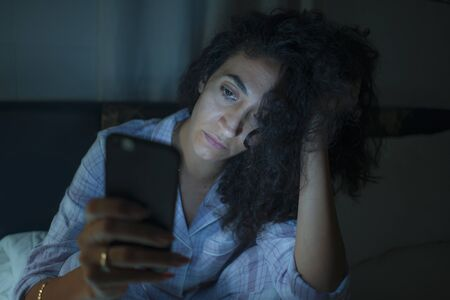 young tired and thoughtful hipster woman on bed late at night using social media app on mobile phone online dating in online addiction and internet overuse and obsession concept