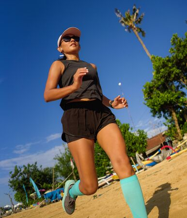 outdoors fitness lifestyle portrait of young attractive and athletic woman in compression running socks jogging on the beach doing intervals workout in athlete training concept and healthy lifestyle