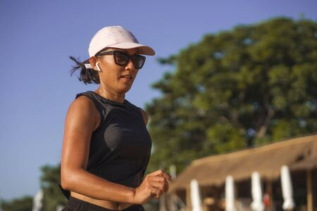 outdoors fitness lifestyle portrait of young attractive and athletic woman jogging happy on city park doing intervals workout in athlete training a running session concept Reklamní fotografie