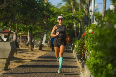 outdoors fitness portrait of young attractive and athletic woman jogging happy on city park doing intervals workout training a running session concept in athlete healthy lifestyle Reklamní fotografie