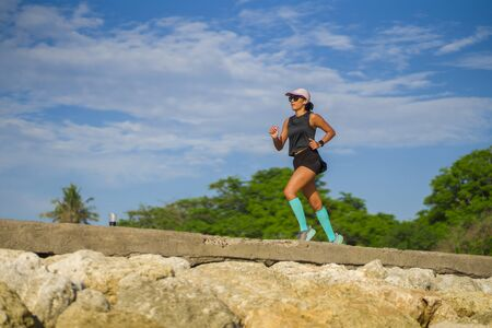 outdoors fitness portrait of young attractive and athletic woman jogging happy on city park doing intervals workout training a running session concept in athlete healthy lifestyle
