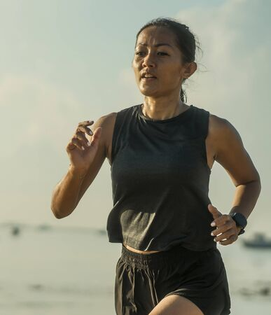outdoors fitness portrait of young attractive and athletic Asian Indonesian woman in her 40s running on the beach doing intervals workout in athlete training concept and healthy lifestyle