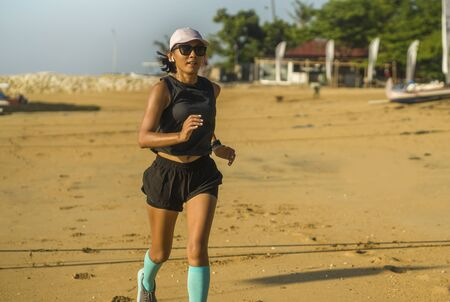 young attractive and happy Asian Indonesian woman in her 40s running happy on the beach enjoying morning jogging workout cheerful and carefree in professional athlete training concept