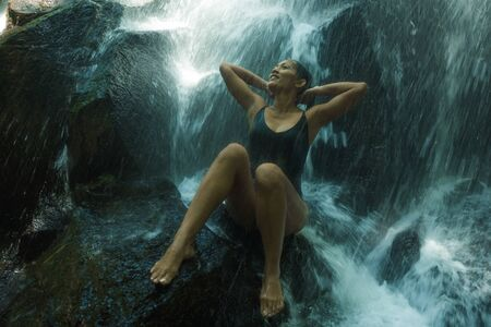 young attractive and blissful Asian Indonesian woman overwhelmed by the beauty of natural waterfall in tropical jungle enjoying happy the amazing and exotic travel destination