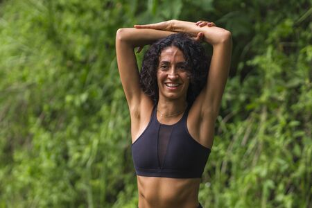 young happy and attractive middle eastern woman with curly hair and athletic body stretching arms outdoors before running workout enjoying nature and clean environment in healthy lifestyle