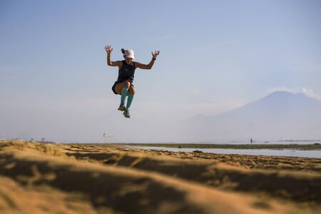 young athletic and attractive crazy happy woman jumping high on the air at beautiful beach enjoying freedom and nature during fitness workout outdoors in healthy lifestyle and vitality concept