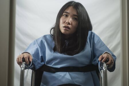 insanity asylum horror movie style portrait of young sick and psychotic Asian Chinese woman isolated and locked in mental hospital security cell sitting on wheelchair suffering schizophrenia