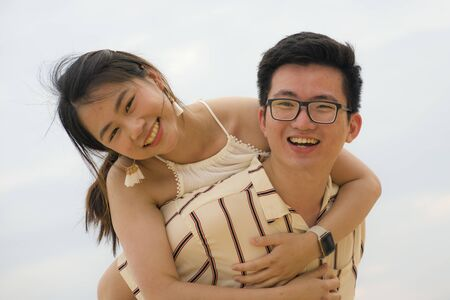 sweet and romantic lifestyle portrait of young happy Asian Chinese couple in love enjoying holiday or weekend with man carrying girlfriend on his back cuddling and playing together