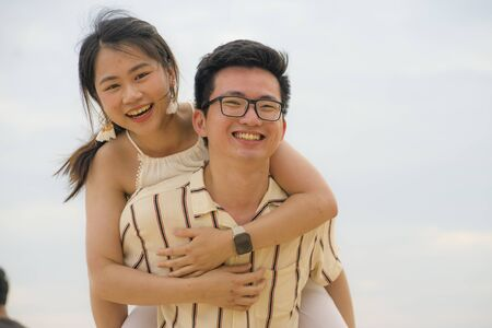 sweet and romantic lifestyle portrait of young happy Asian Korean couple in love enjoying holiday or weekend with man carrying girlfriend on his back cuddling and playing together