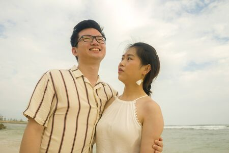 sweet and romantic lifestyle portrait of young Asian Chinese couple in love enjoying holiday on beautiful beach walking together by the sea playful and carefree  in happy relationship concept 版權商用圖片 - 140939565