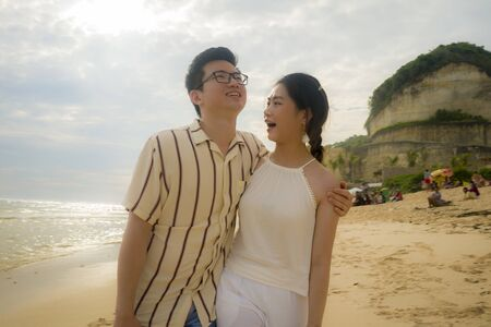 sweet and romantic lifestyle portrait of young happy Asian Chinese couple in love enjoying holiday on beautiful beach walking together by the sea playful and affectionate in relationship concept