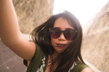 young happy and beautiful Asian Korean Chinese taking selfie photo with mobile phone posing playful and carefree in sunglasses enjoying Summer holiday trip
