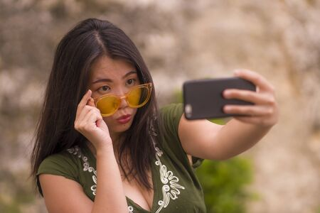 young happy and beautiful Asian Korean woman taking selfie photo with mobile phone posing playful and carefree in hipster sunglasses enjoying Summer holiday trip