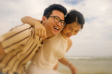 sweet and romantic lifestyle portrait of young Asian Chinese couple in love enjoying holiday on beautiful beach walking together by the sea playful and carefree  in happy relationship concept