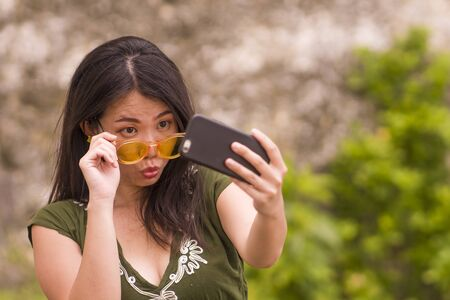 young happy and beautiful Asian Chinese woman taking selfie photo with mobile phone posing playful and carefree in hipster sunglasses enjoying Summer holiday trip 版權商用圖片
