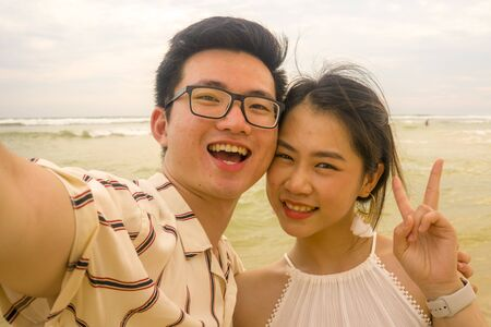young happy and romantic Asian Korean couple in love enjoying holiday taking selfie photo together on beautiful beach having fun by the sea playful and affectionate in relationship concept