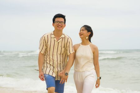sweet and romantic lifestyle portrait of young happy Asian Korean couple in love enjoying holiday on beautiful beach walking together by the sea playful and affectionate in relationship concept 版權商用圖片 - 140939388