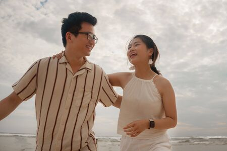 sweet and romantic lifestyle portrait of young Asian Korean couple in love enjoying holiday on beautiful beach walking together by the sea playful and carefree  in happy relationship concept