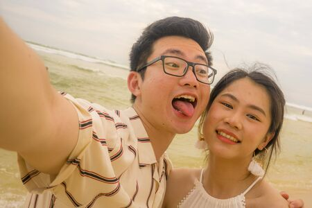 young happy and romantic Asian Chinese couple in love enjoying holiday taking selfie photo together on beautiful beach having fun by the sea playful and affectionate in relationship concept