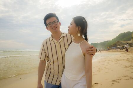 sweet and romantic lifestyle portrait of young happy Asian Korean couple in love enjoying holiday on beautiful beach walking together by the sea playful and affectionate in relationship concept 版權商用圖片