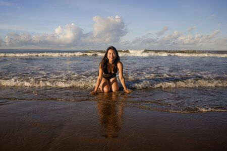 natural lifestyle portrait of young attractive and happy Asian Chinese woman in swimsuit kneeling on sand at beautiful beach paradise feeling relaxed and cheerful enjoying holidays carefree